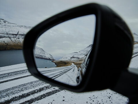 Side mirror of car with view of snowy road in the Faroe Islands