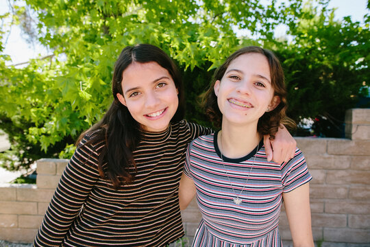 Teen and Tween Sisters Wearing Stripes Smile For The Camera
