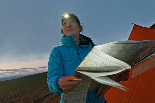 female hiker reading hiking map on Pen Y Fan in Wales at sunrise