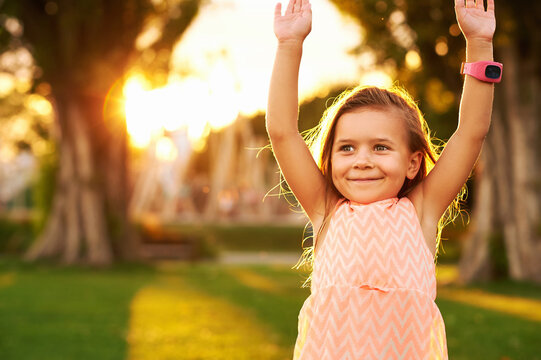 Outdoor portrait of adorable 3 or 4 year old girl playing in summer park, raised arms, wearing smart watch, beautiful sunlight on bright green lawn