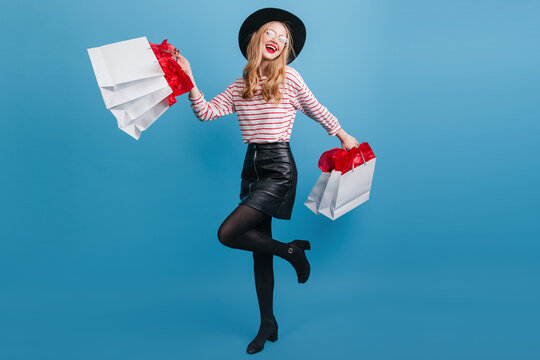 Blissful blonde girl in leather skirt dancing on blue background. Studio shot of joyful young woman with shopping bags.