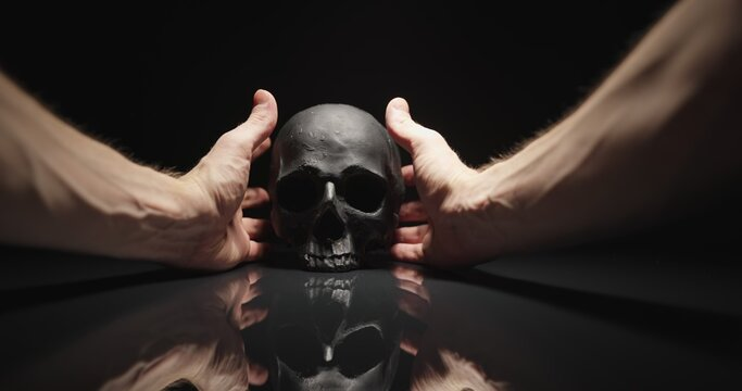 Hands reaching for black skull with reflection
