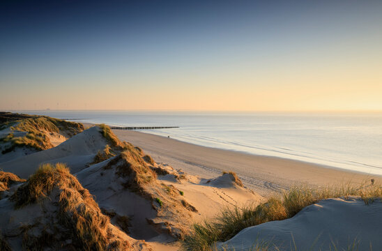 sea, beach and dunes at sunset