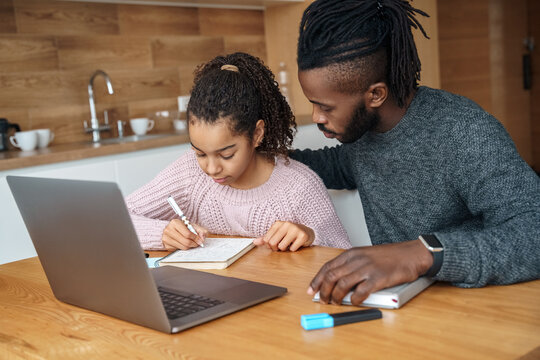 Happy African American father helps to study online to his teen age daughter.