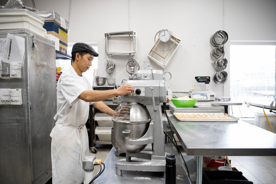 Male baker using commercial mixer in bakery kitchen