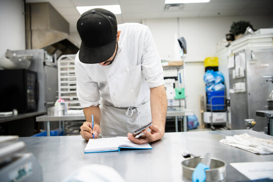 Male baker with smart phone and notebook planning in bakery kitchen