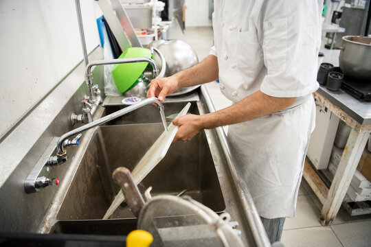 Male chef washing cutting board at sink in commercial bakery kitchen