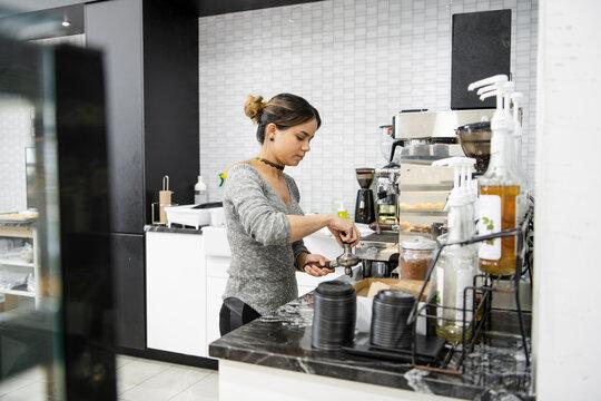 Female bakery owner preparing espresso at espresso machine
