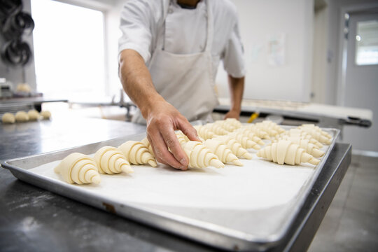 Male baker arranging croissant dough on sheet pan in bakery kitchen
