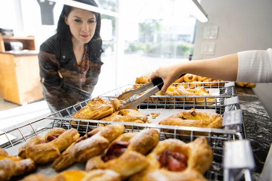 Female customer watching bakery worker serve pastries