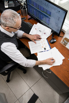 Male business owner reviewing purchase order paperwork in office