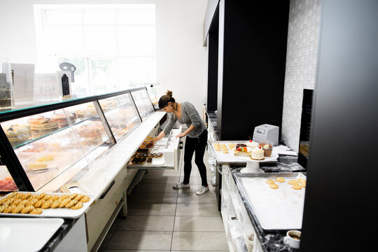 Female bakery owner arranging French pastries in display case