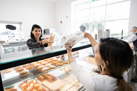 Female bakery worker serving customer at display case