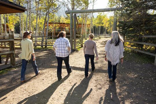Mature women friends walking on sunny autumn ranch