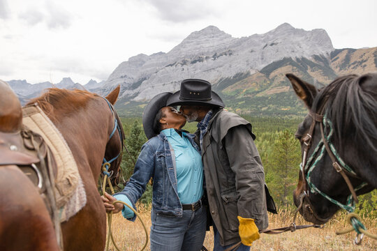 Affectionate senior couple kissing on horseback ride in mountains