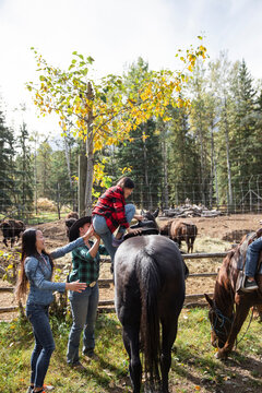 Mother and rancher helping girl mount horse on sunny autumn ranch