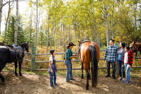 Rancher helping family prepare for horseback riding on autumn ranch