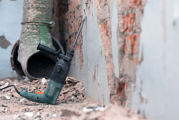 Hammer drill with chisel on the old brick wall background. Removing an old putty from the wall...
