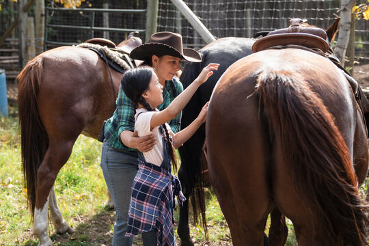 Rancher helping girl prepare for horseback riding on sunny ranch