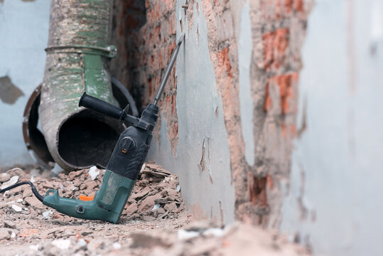 Hammer drill with chisel on the old brick wall background. Removing an old putty from the wall background.