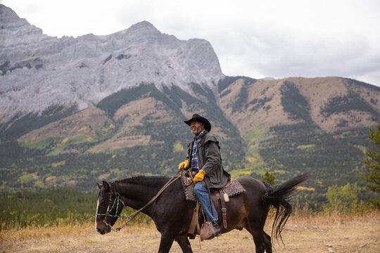 Happy senior man horseback riding on scenic mountain trail