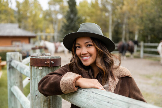 Portrait happy young woman in hat at rural horse ranch fence
