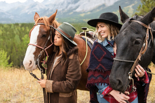 Young women in hats friends horseback riding