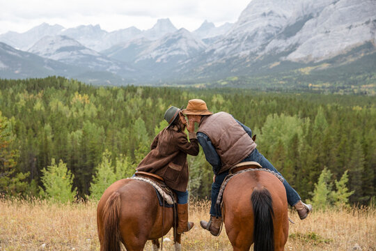 Affectionate young couple kissing on horseback in scenic mountains