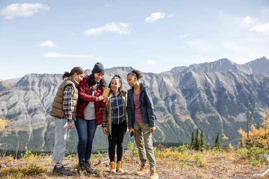 Mother and daughter hikers using smart phone on scenic mountain summit