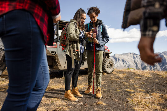 Mother and daughter hikers using smart phone on sunny mountain