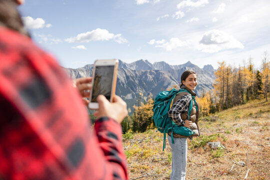 Mother photographing happy daughter hiking in autumn Canadian Rockies
