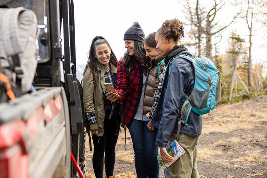 Mother and daughter hikers with smart phone at SUV