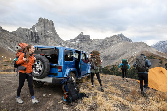 Female backpackers outside jeep in majestic Rocky Mountains, Canada