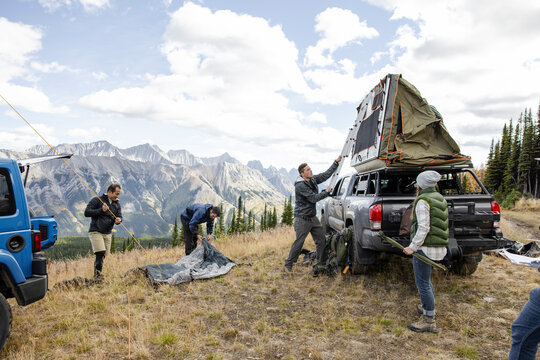 Friends preparing camping tents in scenic majestic mountains