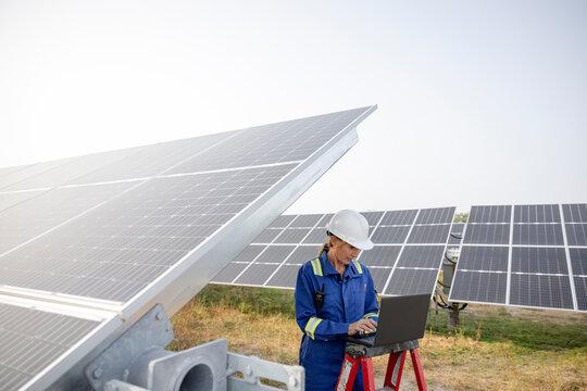 Technician working on laptop in solar farm