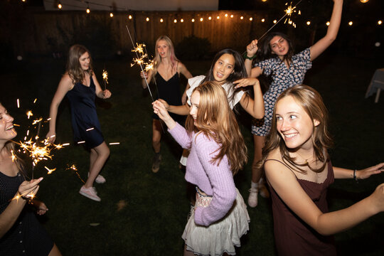 Carefree teenage girl friends dancing with sparklers at night