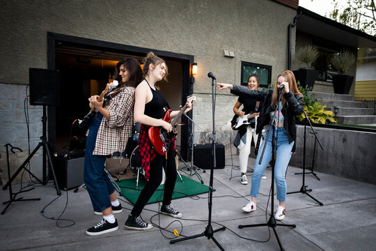 Teenage girl friends playing guitars as rock band in house driveway