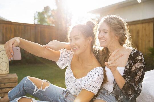 Happy playful teenage girl friends taking selfie in sunny backyard