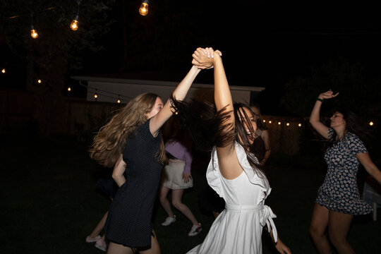 Carefree teenage girl friends dancing at backyard night party