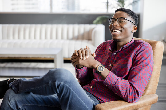 Happy young businessman laughing in office