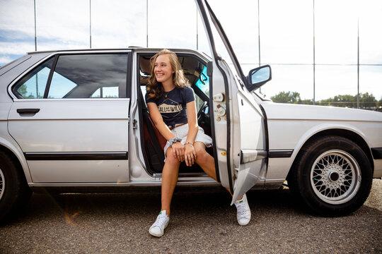 Happy teenage girl sitting in open car doorway