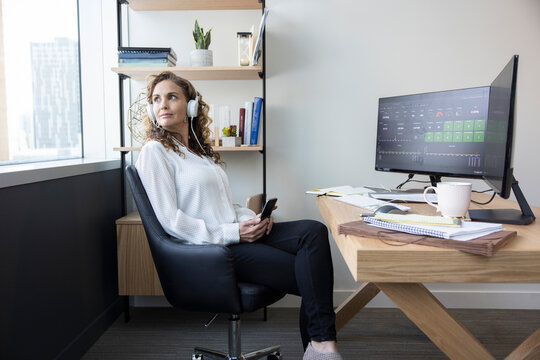 Thoughtful businesswoman with headphones and smart phone in office