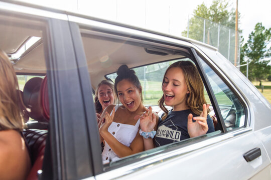 Happy teenage girl friends singing in back seat of sunny car