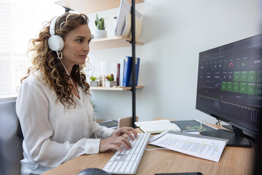 Businesswoman with headphones working at computer in office