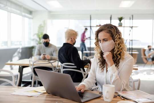 Businesswoman in face mask working at laptop in coworking space