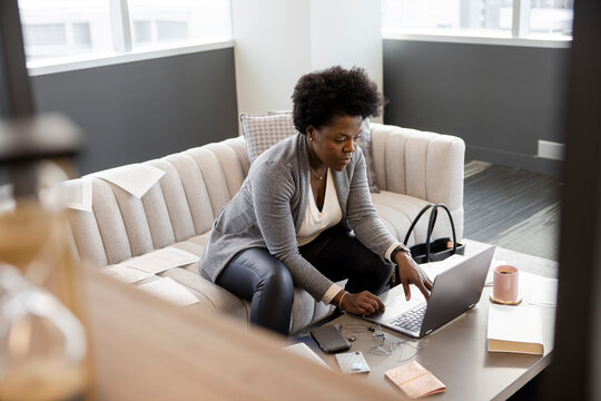 Businesswoman working at laptop on office sofa