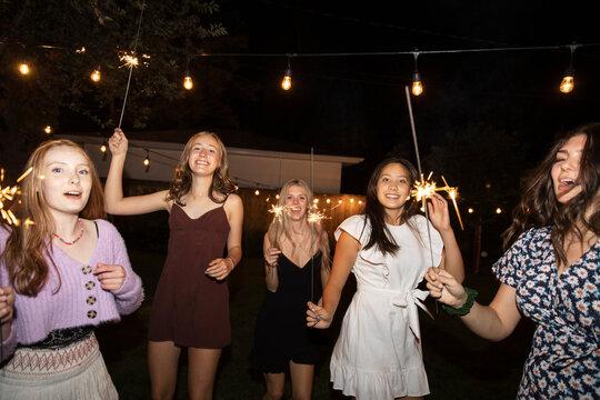 Portrait happy teenage girl friends dancing with sparklers in backyard