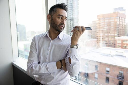 Businessman talking on smart phone speaker at highrise office window