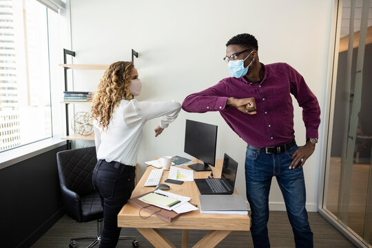 Business people in face masks elbow bumping over office desk