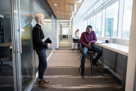 Young businessmen talking in office corridor